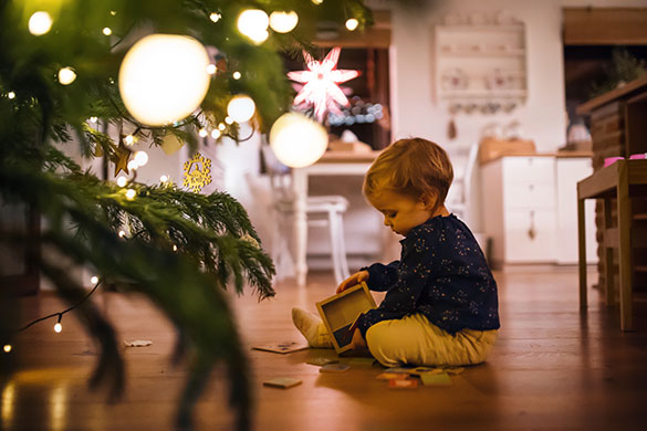 child playing on floor by christmas tree