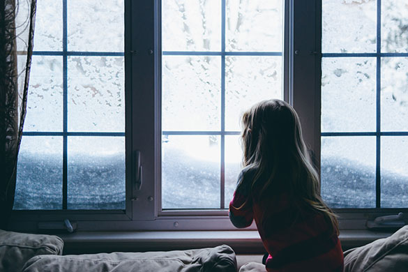 little girl looking out window on snowy day