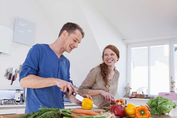 man and woman cutting vegetables