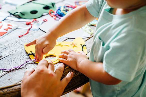 child doing craft with parent