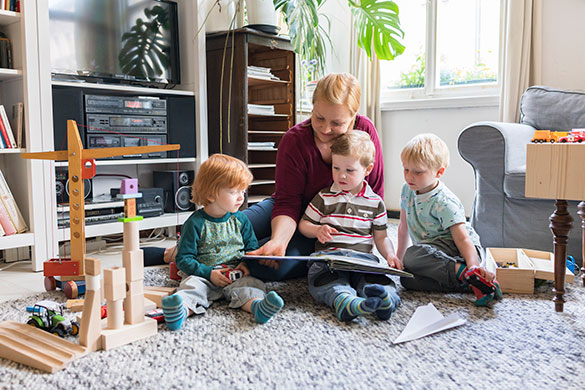 mother reading with her three boys