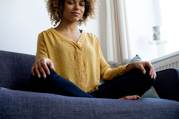 young woman meditating at home on couch