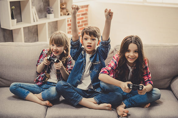 kids sitting on couch gaming