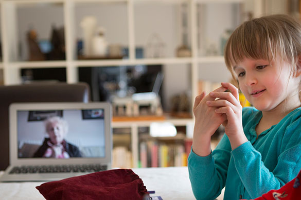 child playing game with grandma via video call