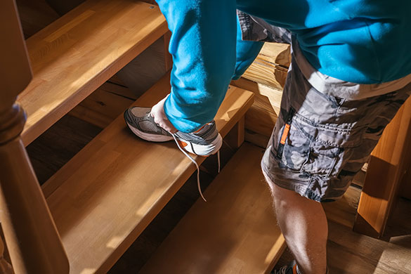 closeup of man tying shoes on stairs