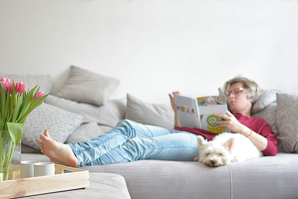woman laying on couch with dog reading book