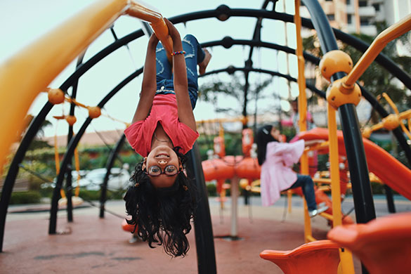 girl hanging upside down on jungle gym