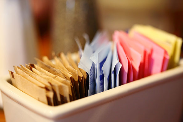 close-up of sweetener packets in container