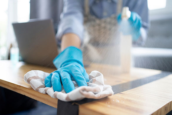 closeup of person cleaning table with disinfectant spray