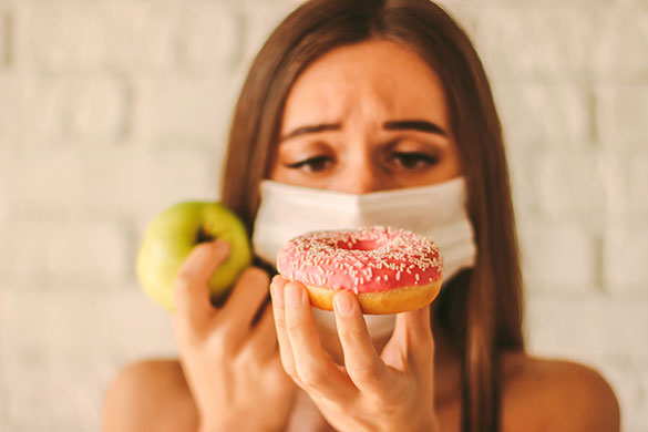 woman deciding between apple and donut