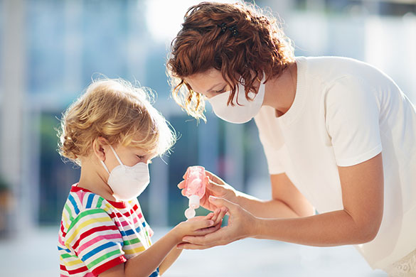 mother and child with face masks and hand sanitizer