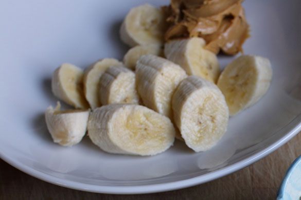 cut up banana and peanut butter on a plate