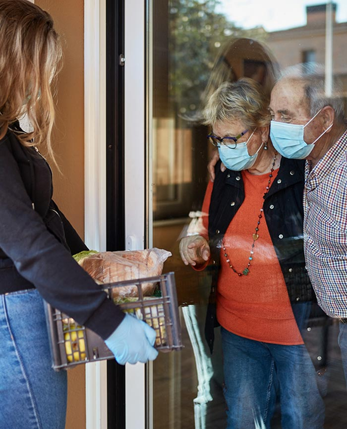 woman making delivery to couple wearing masks