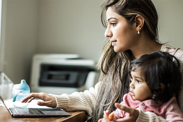mom working on laptop daughter on her lap