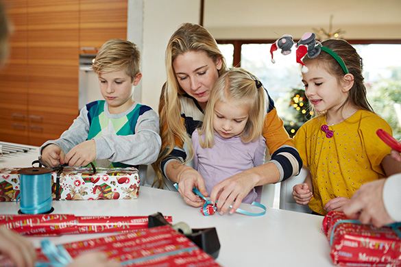 mom wrapping presents with kids