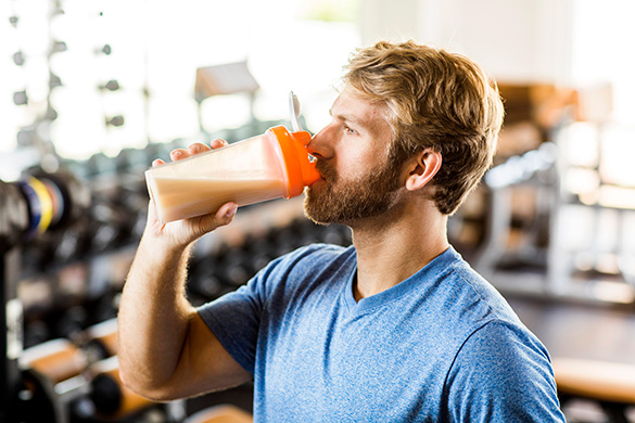 man drinking sports drink in gym