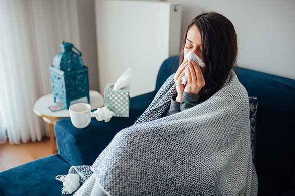 sick woman blowing nose wrapped in blanket