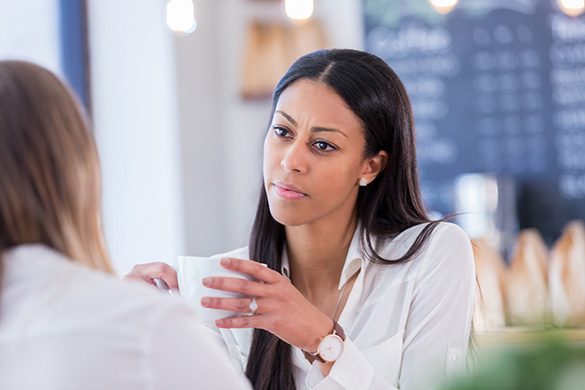 concerned young woman talks to friend in coffeeshop