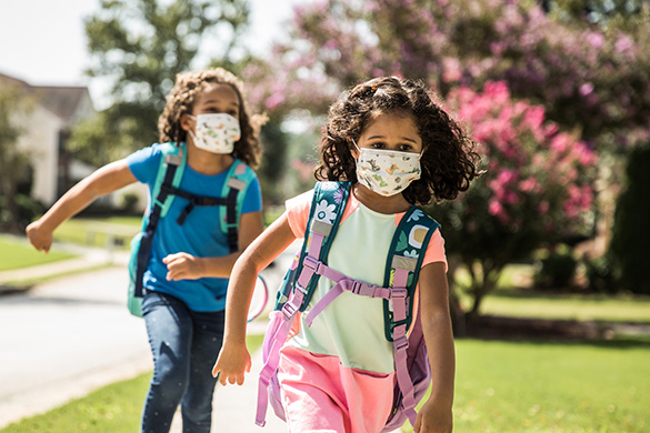 two girls running to school wearing backpacks and masks